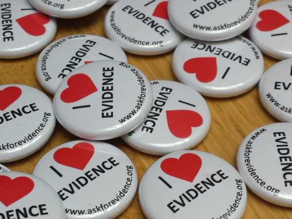 Pile of badges that have 'I heart Evidence' printed on them