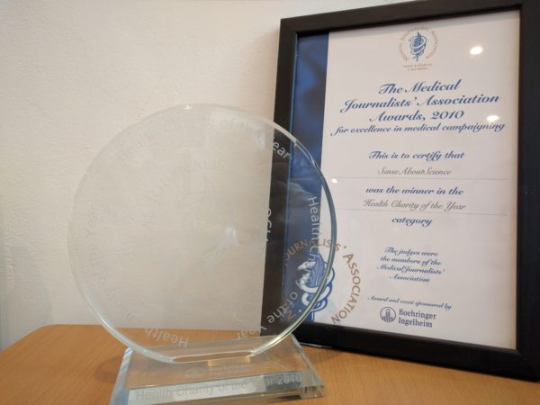 Photograph of round glass award and framed certificate