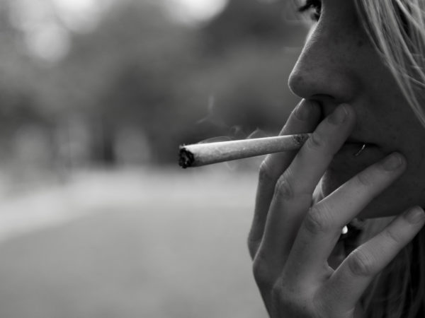Black and white close up of woman smoking.