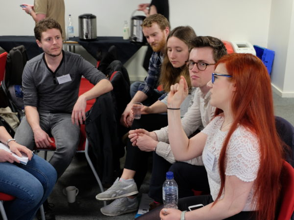 Woman with red hair talking and gesturing to group of early career researchers