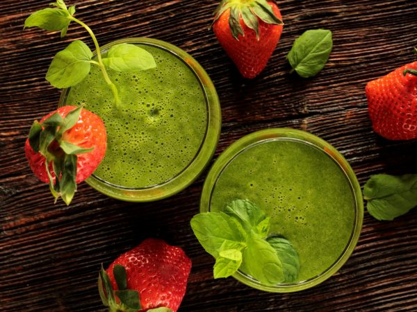 birds-eye view of two glasses of green juice surrounded by strawberries