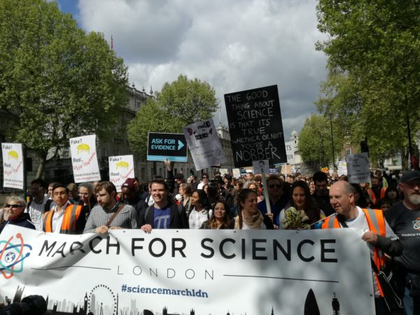March for Science banner with Ask for Evidence placard in view