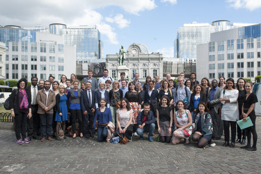 Group of early career researchers and standing up for science panellists standing together on cobbled square in Brussels